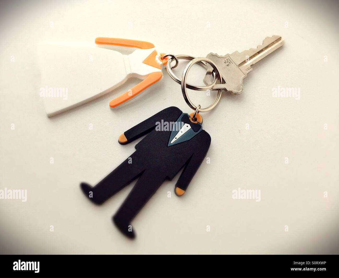 Two key rings in the shape of a bride and groom joined and sharing one key. - Stock Image