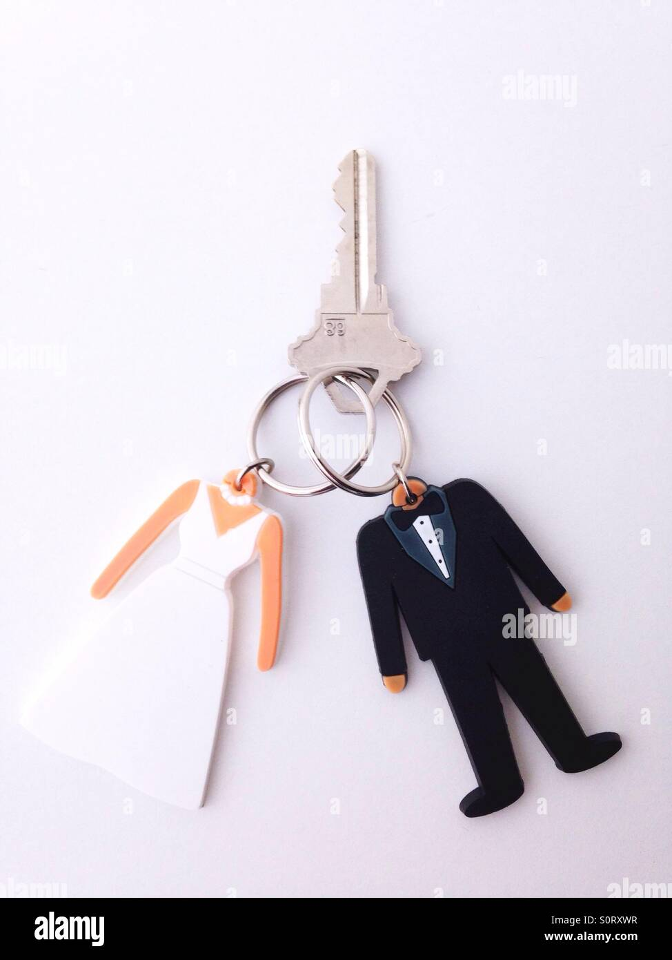 Two key rings in the shape of a bride and groom joined together with one key. - Stock Image