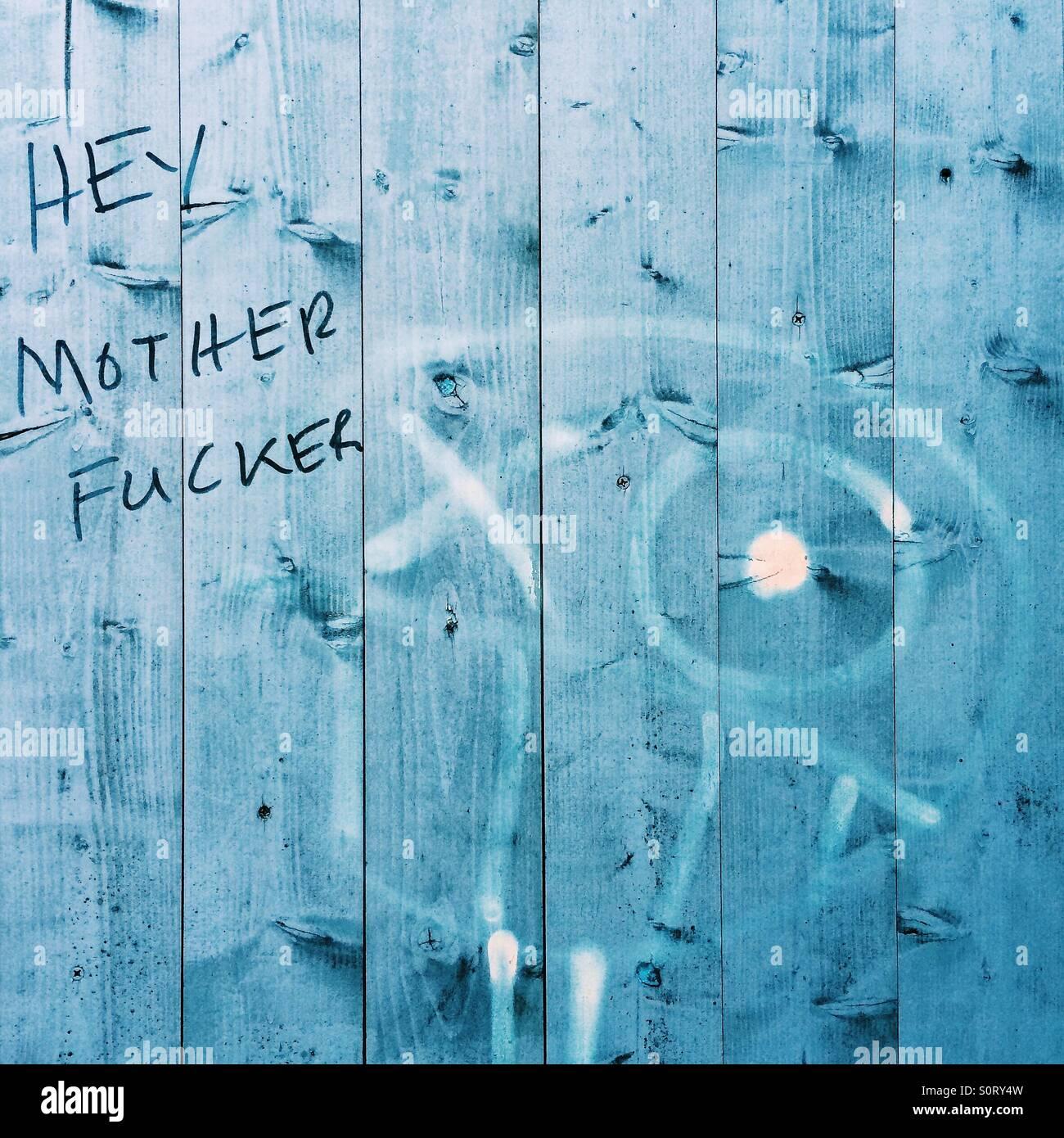 Colourful language graffiti on blue fence - Stock Image