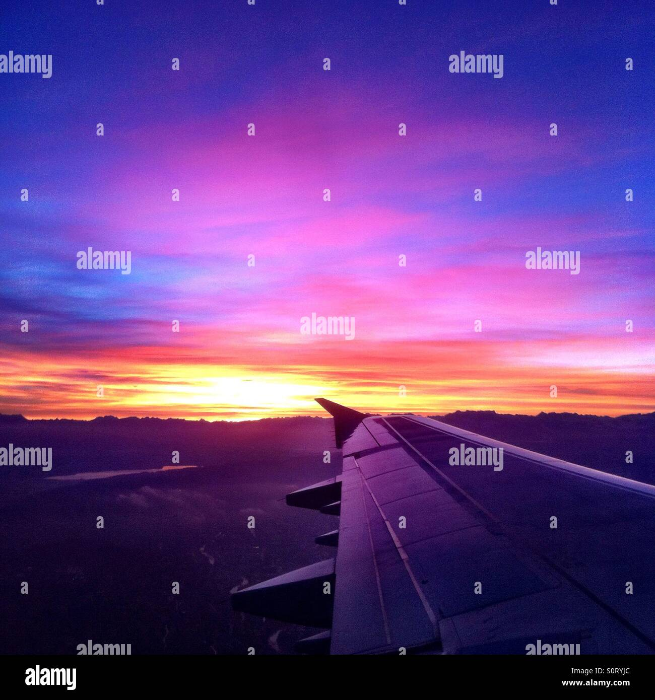 Beautiful sunrise at take off from Zurich, Switzerland, showing wing and mountains. Stock Photo
