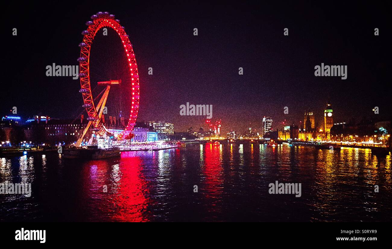 London Eye illuminated and River Thames view and reflections at night on the Embankment in Westminster in the West - Stock Image