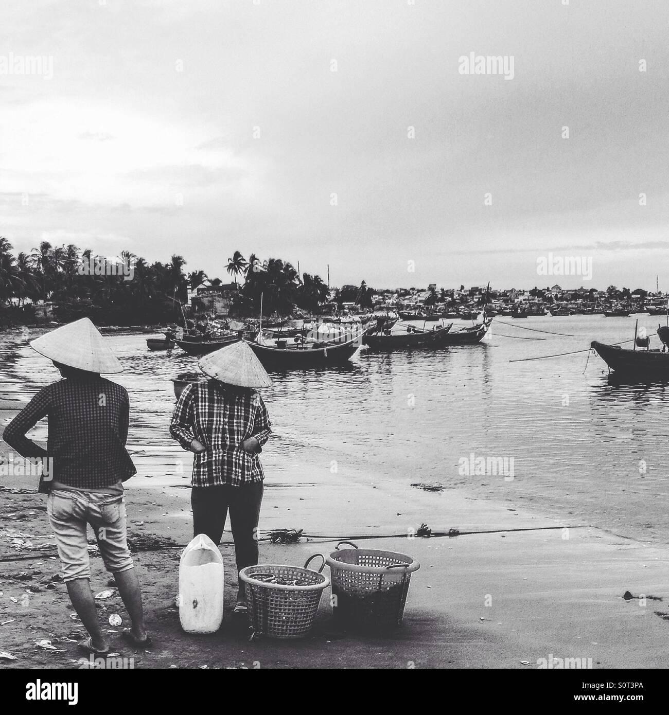 Fishing village Mui Ne Vietnam. Black and white image of local fisherwomen and bay scene - Stock Image