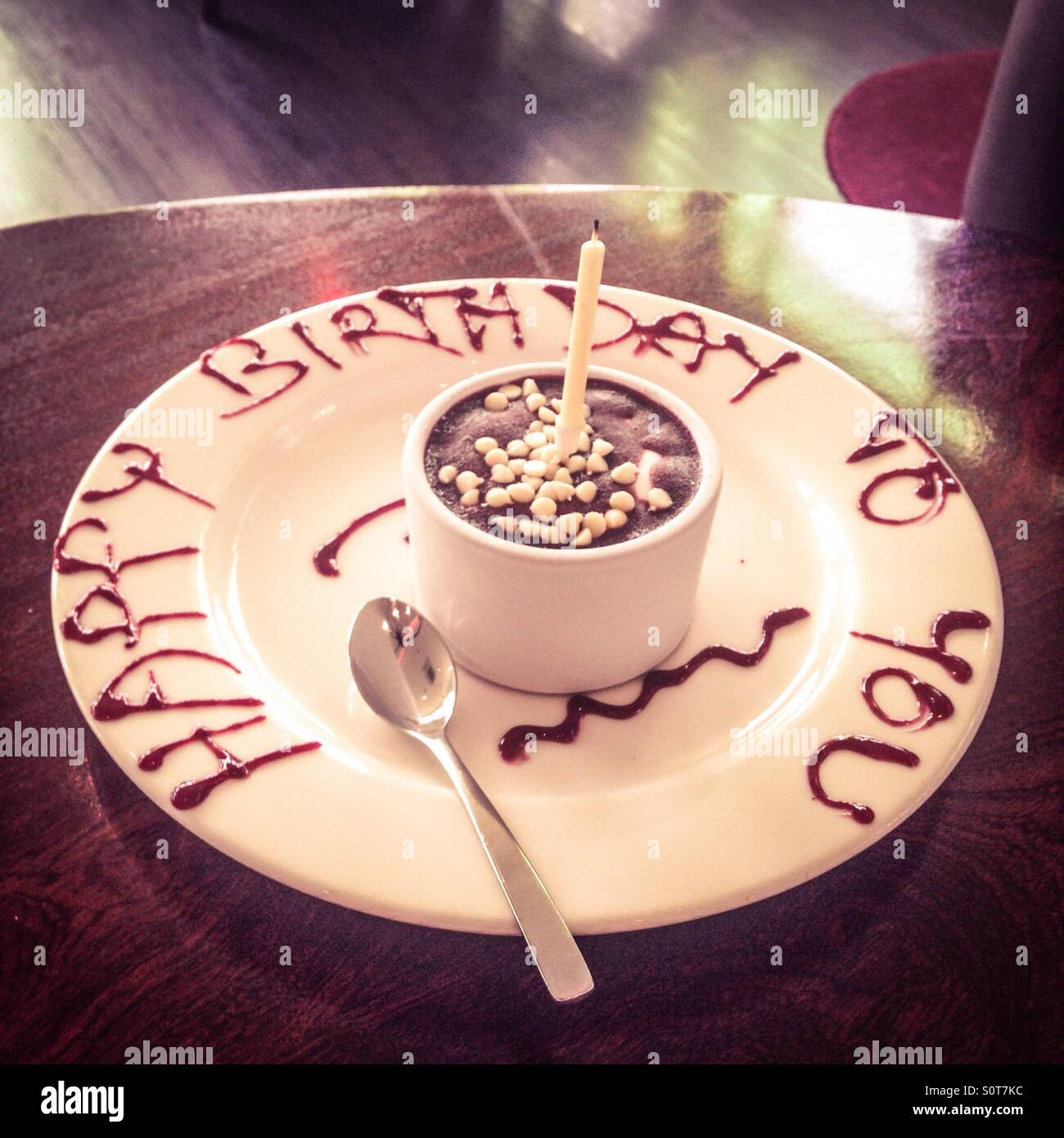 Happy Birthday To You Written On A Plate With Chocolate Sauce And Small Cake In Dish One Candle Spoon Wooden Table