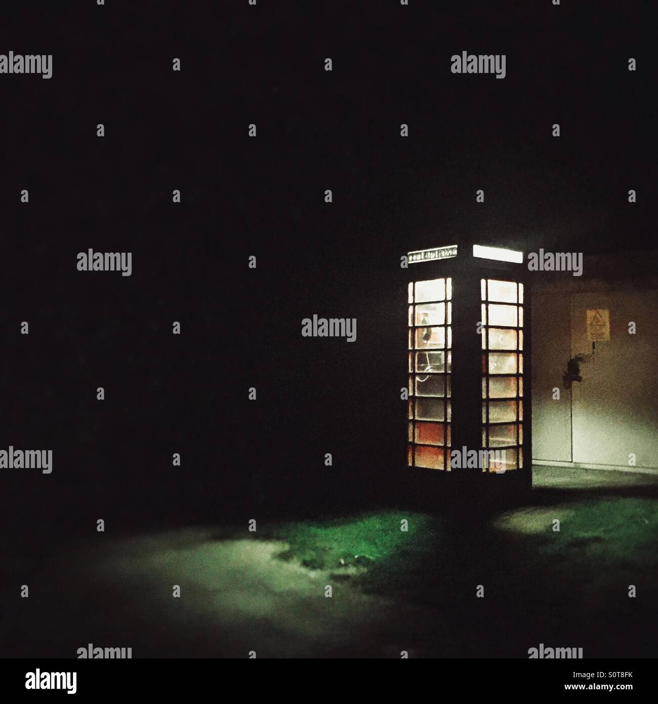 Telephone box at night with light spilling out - Stock Image