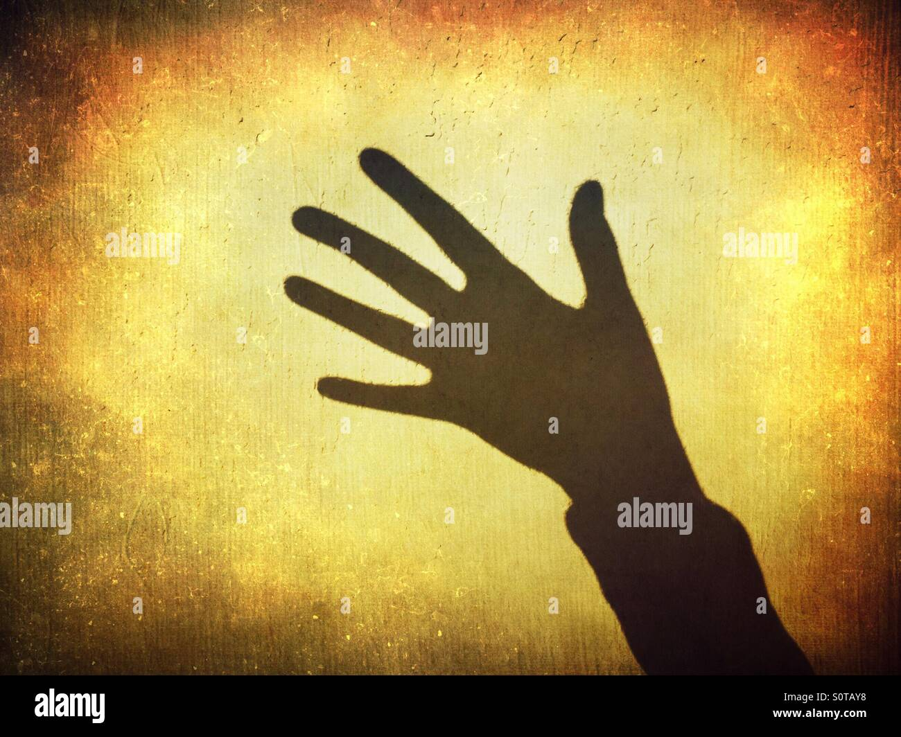 Shadow of a hand showing five fingers - Stock Image