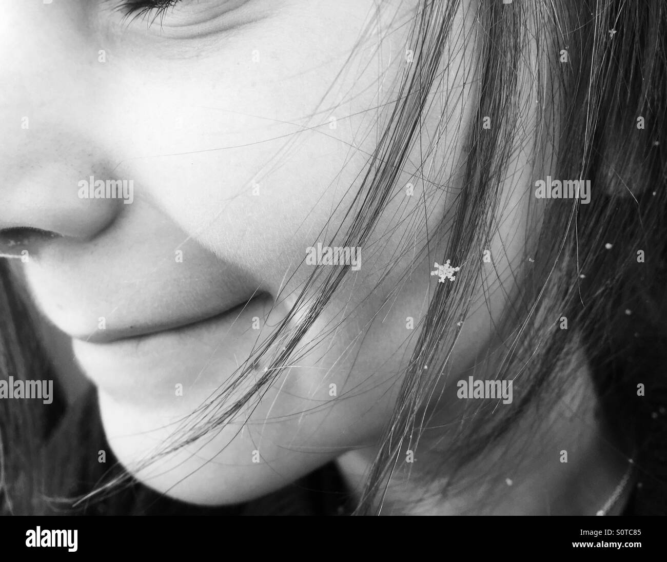 A perfect little snowflake in a young girl's long hair. - Stock Image