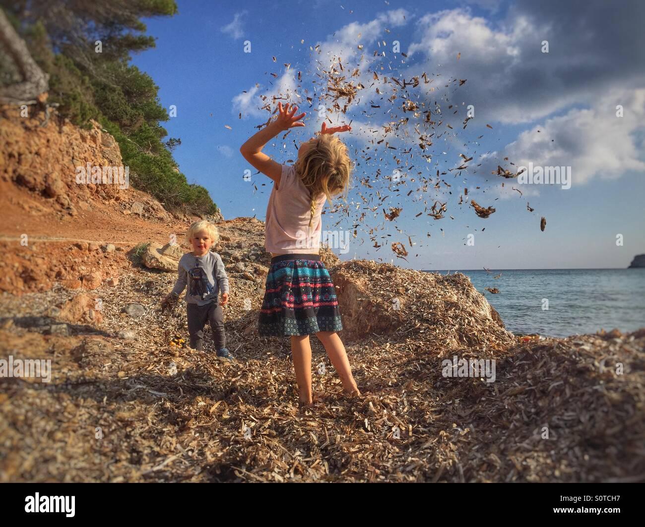 Kids throwing seaweed - Stock Image