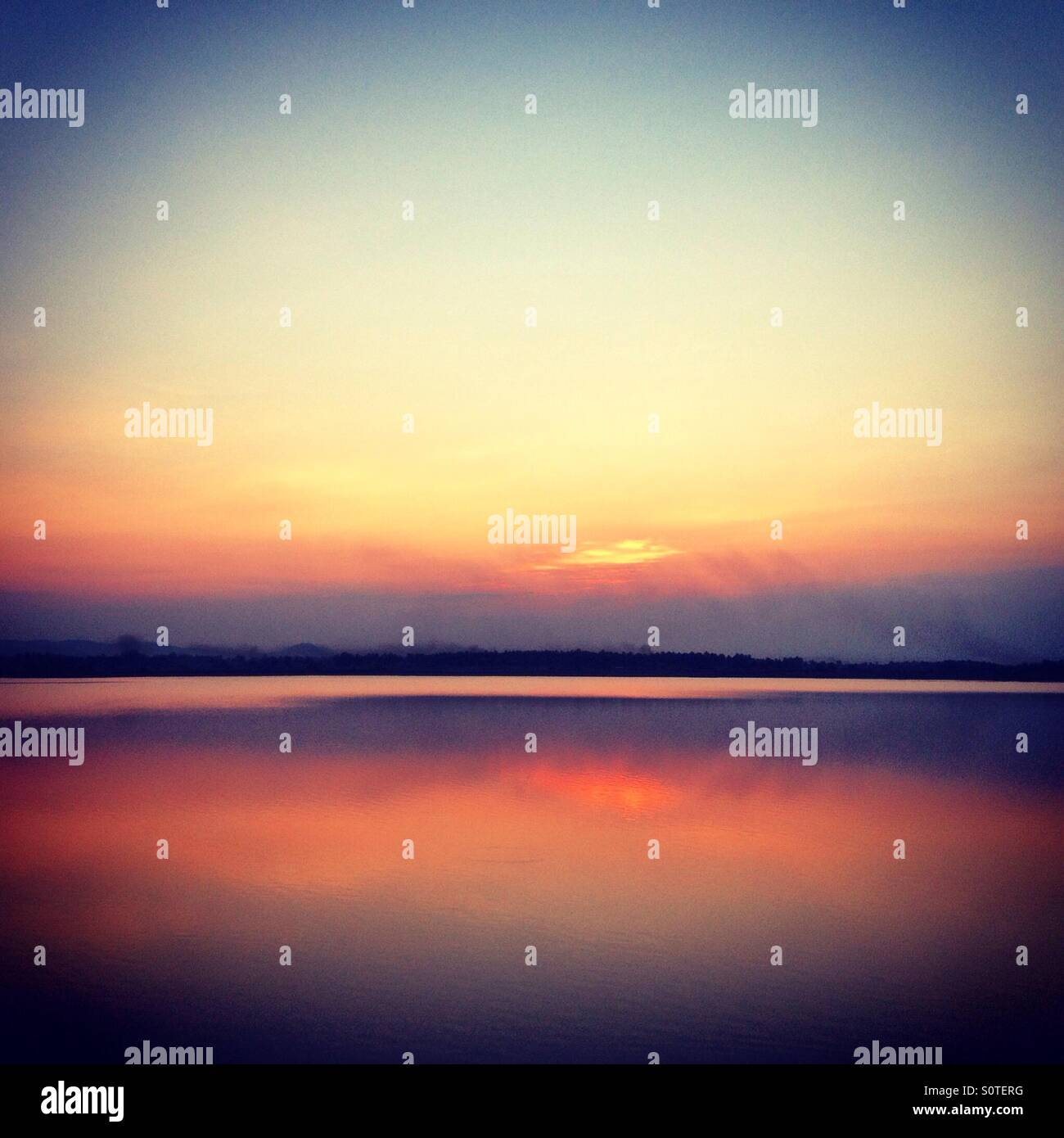 Sunset on a still lake in India - Stock Image