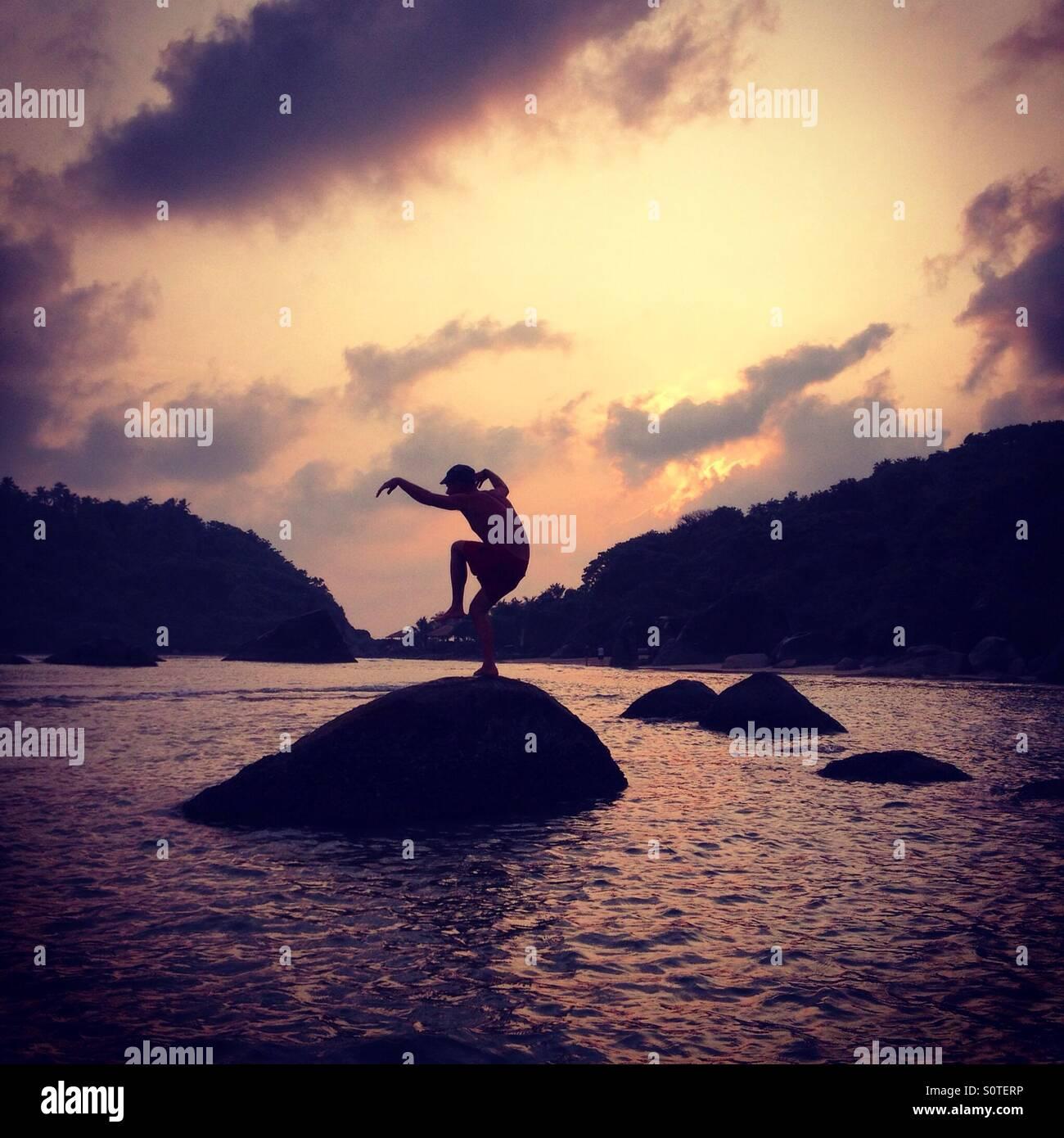 Man balancing on rocks in the sea on Palolem Beach, Goa - Stock Image