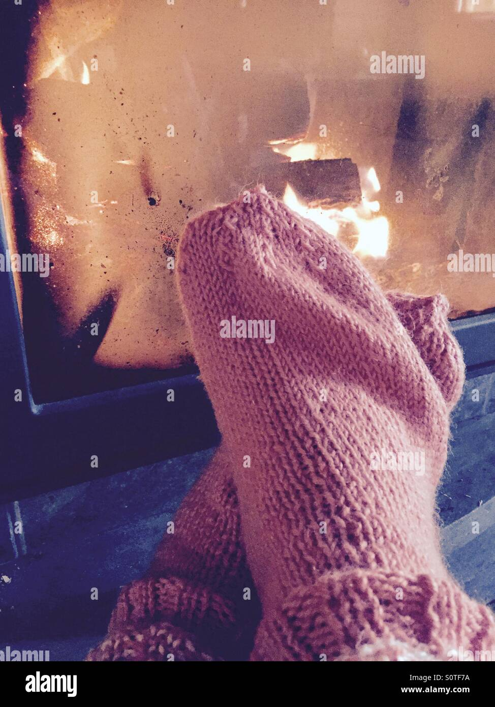 Warming up by a fire place wearing wool socks made by grandmother - Stock Image