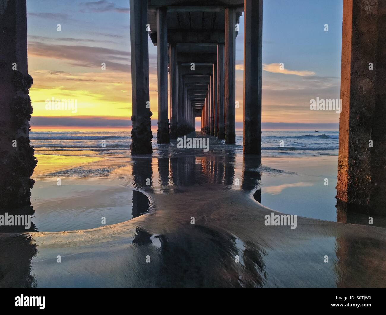 Underneath a beach pier at sunset with water reflections, Scripps Pier, California, USA Stock Photo