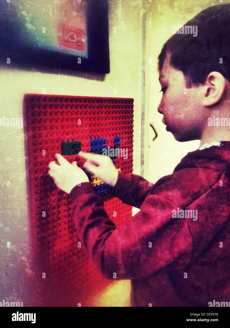 A young boy playing with building blocks in a waiting room. Stock Photo