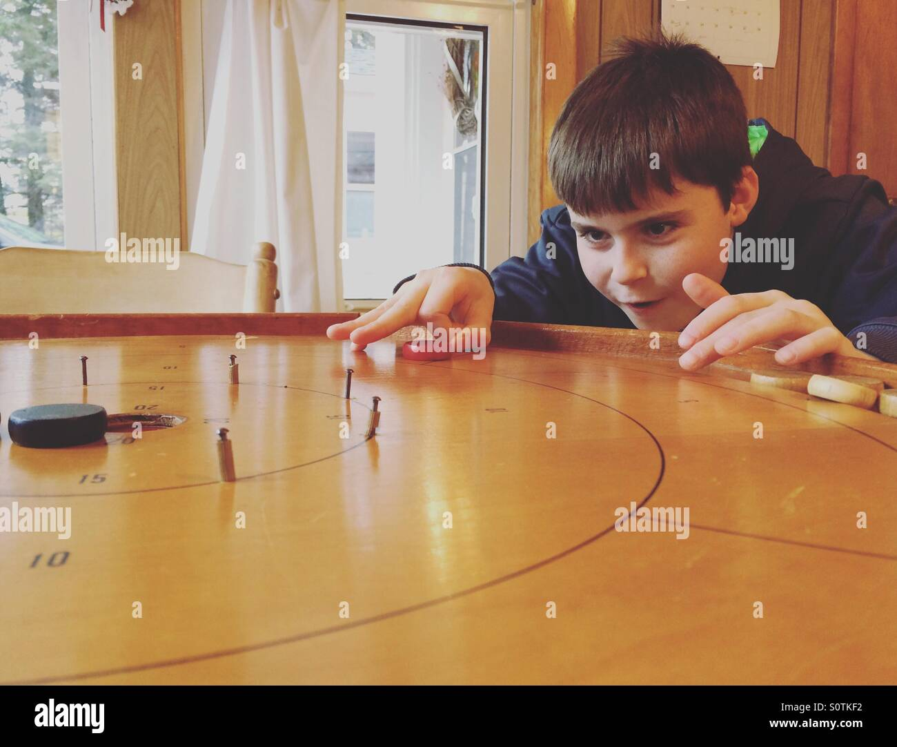 A ten year old boy takes aim at an opponent's disc in a game of crokinole. - Stock Image