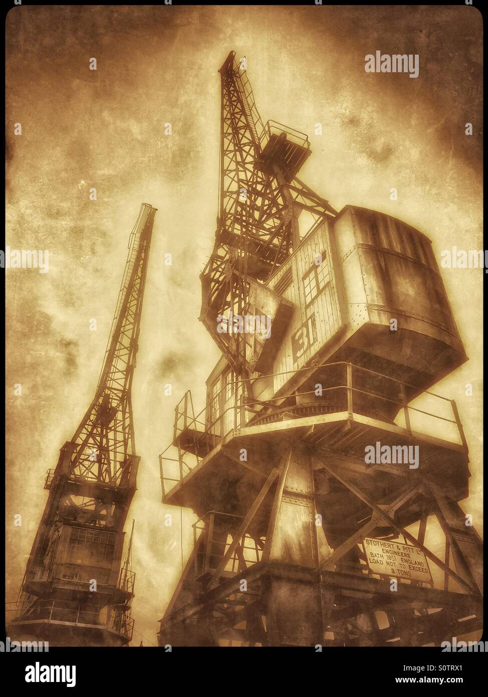 A Sepia Antique Effect Picture of Two Cranes that are situated on the edge of The Floating Harbour, close to the - Stock Image