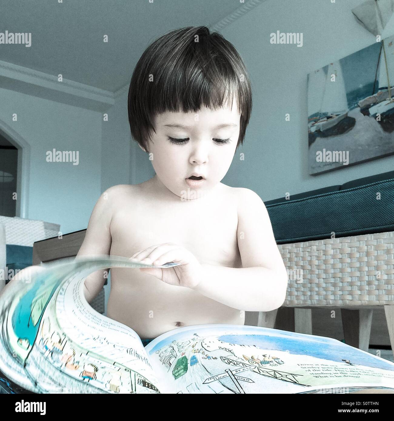 A little boy reading a book - Stock Image