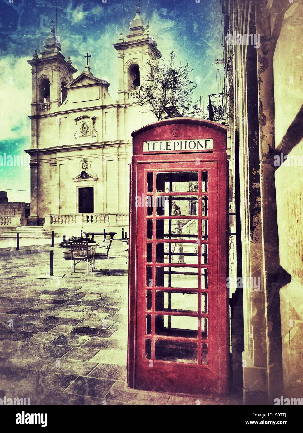 Conceptual image of red telephone box and church - Stock Image