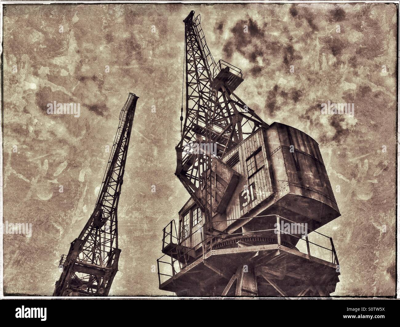 Two of the Cranes situated on the edge of The Floating Harbour in Bristol, England. A Grunge Effect Picture to Illustrate - Stock Image