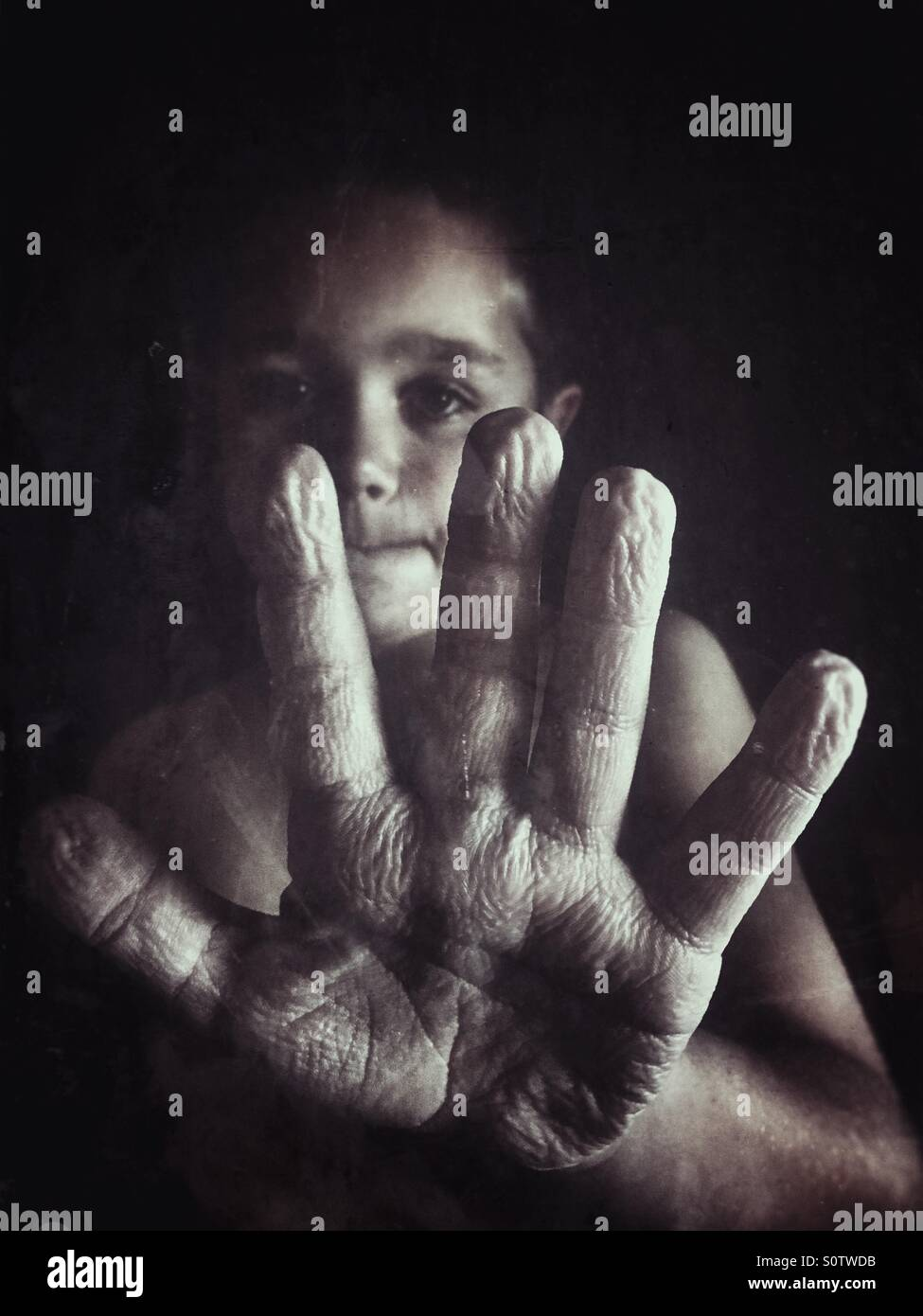 Boy showing wrinkled hand from taking a long shower - Stock Image