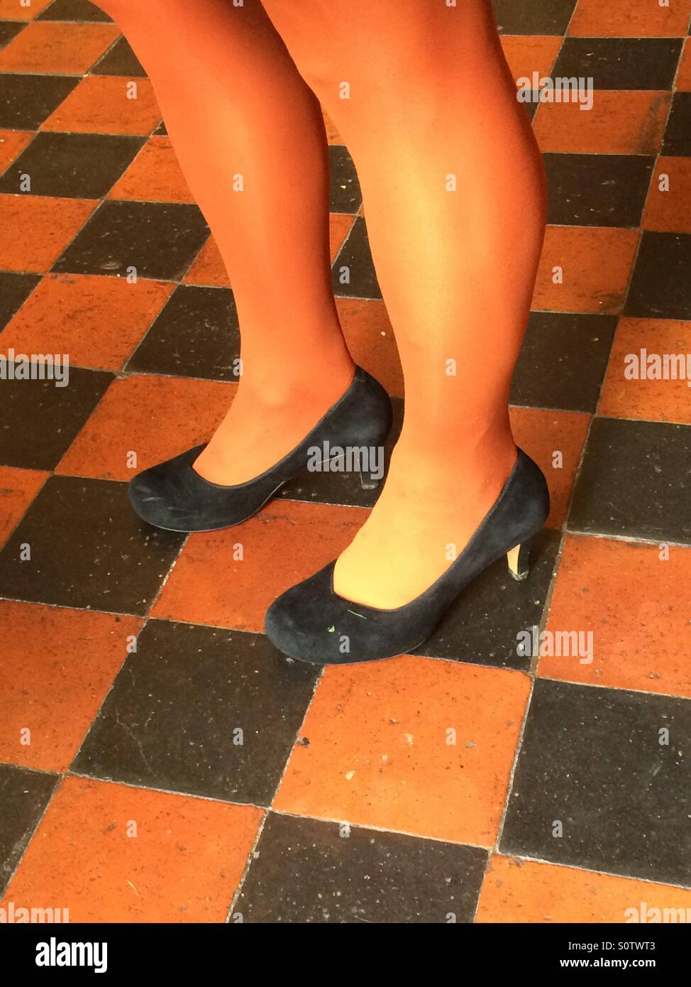 Woman wearing orange tights and black shoes standing on black and orange floor tiles - Stock Image