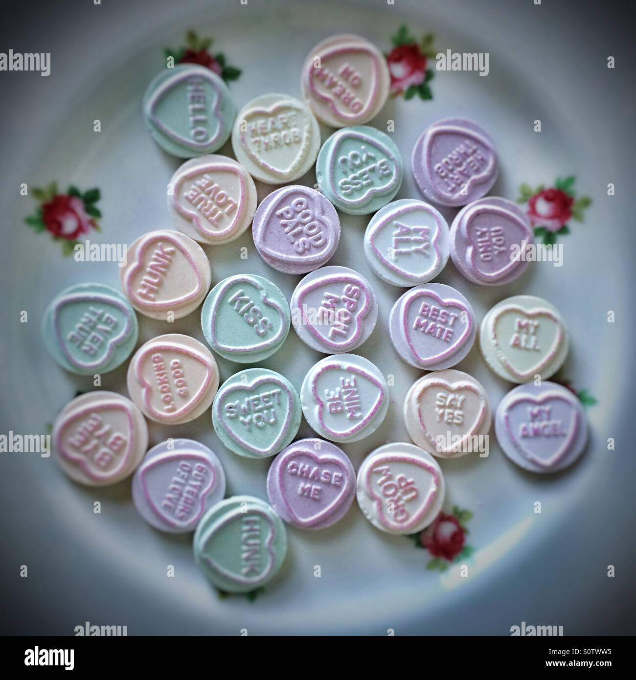 Pretty plate full of love heart candy sweets - Stock Image