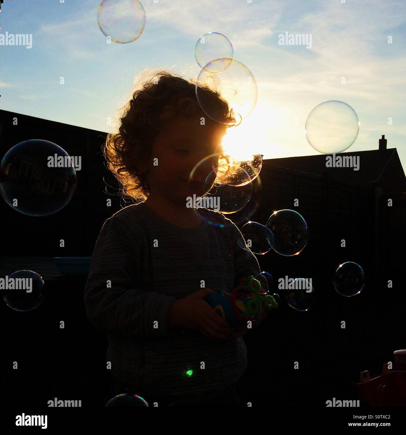 Silhouetted child playing with bubbles in garden - Stock Image