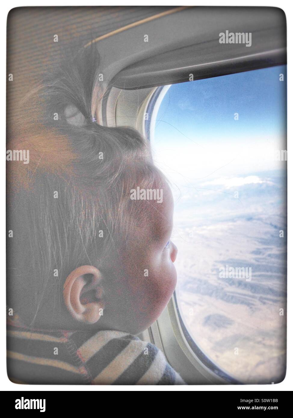 Baby looking out an airplane window - Stock Image