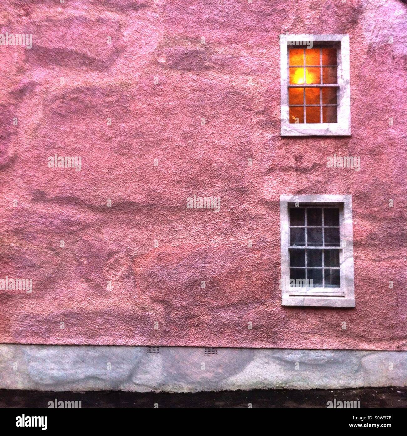 Pink wall with two windows superimposed onto a close up photograph of another wall using the Diana Photo App - Stock Image