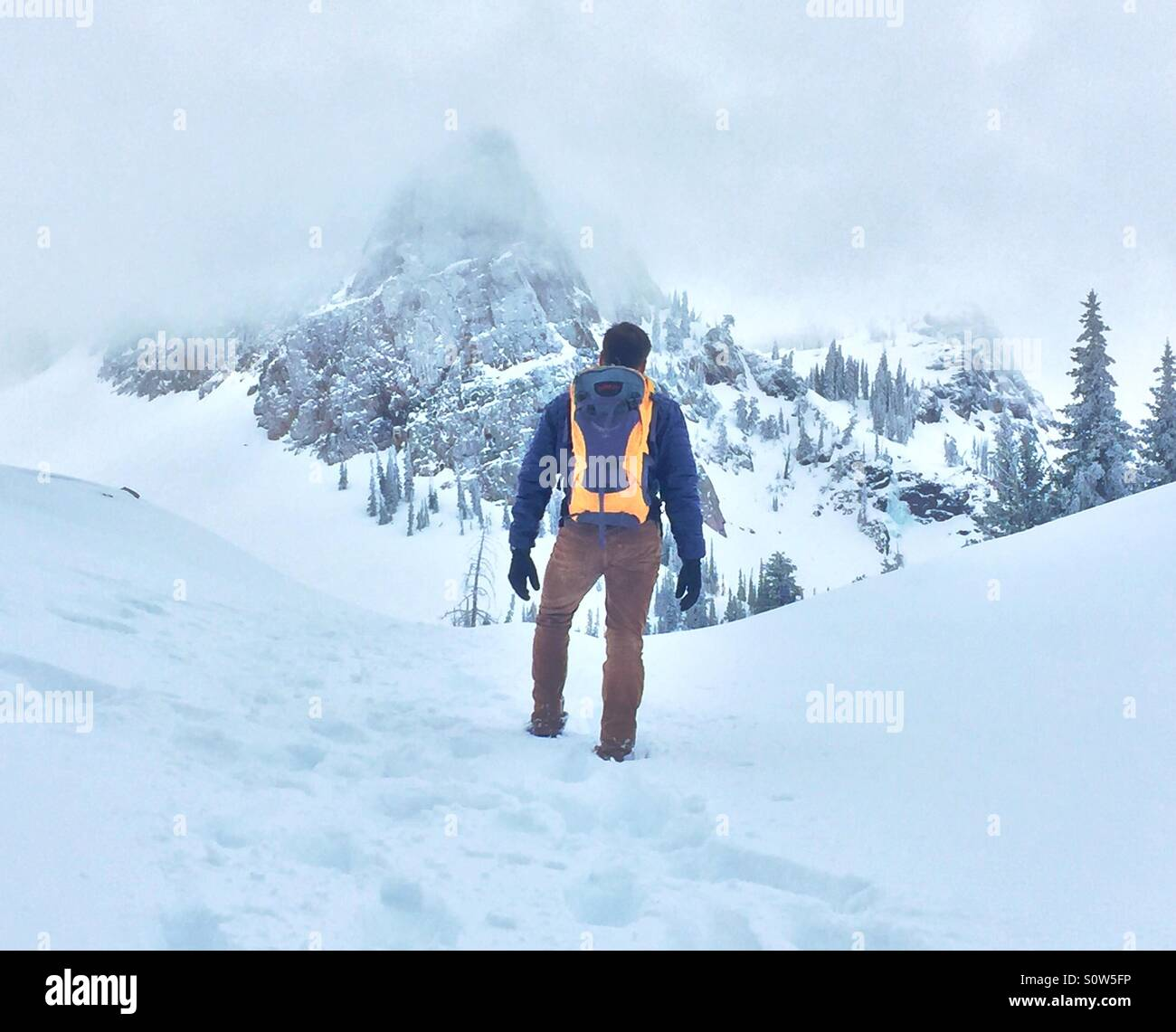 A man hikes up to a mountain peak in snow-covered Utah. - Stock Image