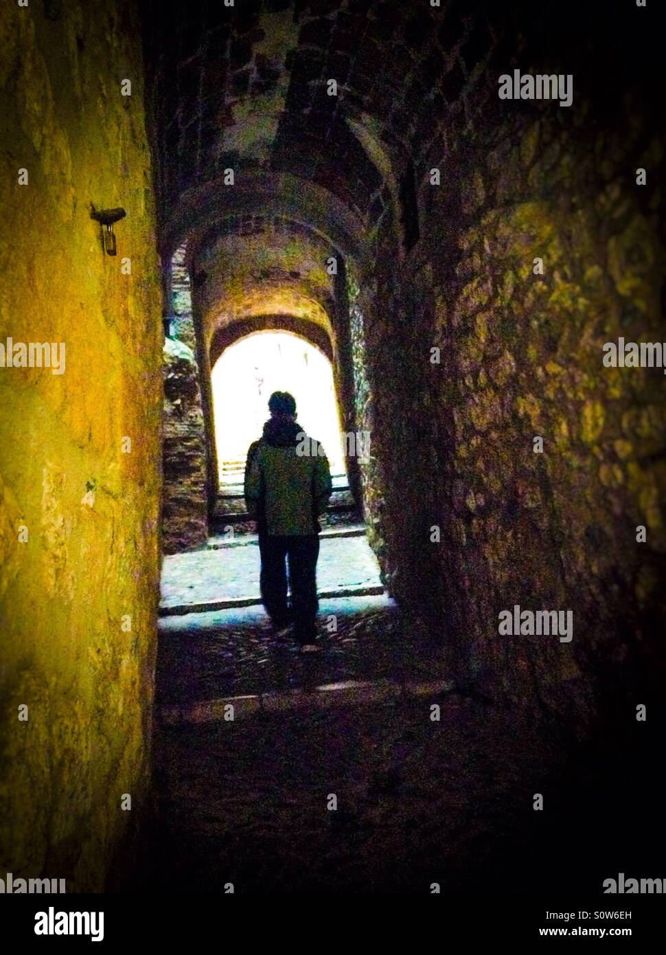 Single silhouette walking through a dark alley in the Call (jewish quarter), Girona, Catalonia Stock Photo