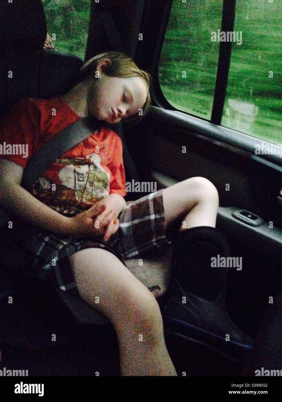 Boy sleeping in car during road trip - Stock Image