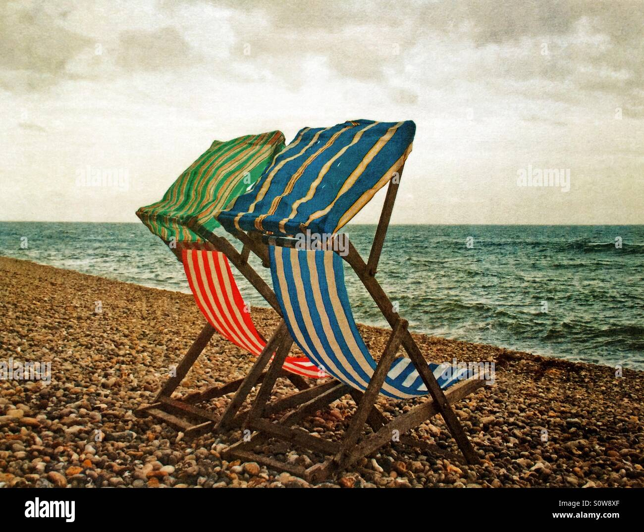 Old worn deckchairs winters day UK - Stock Image