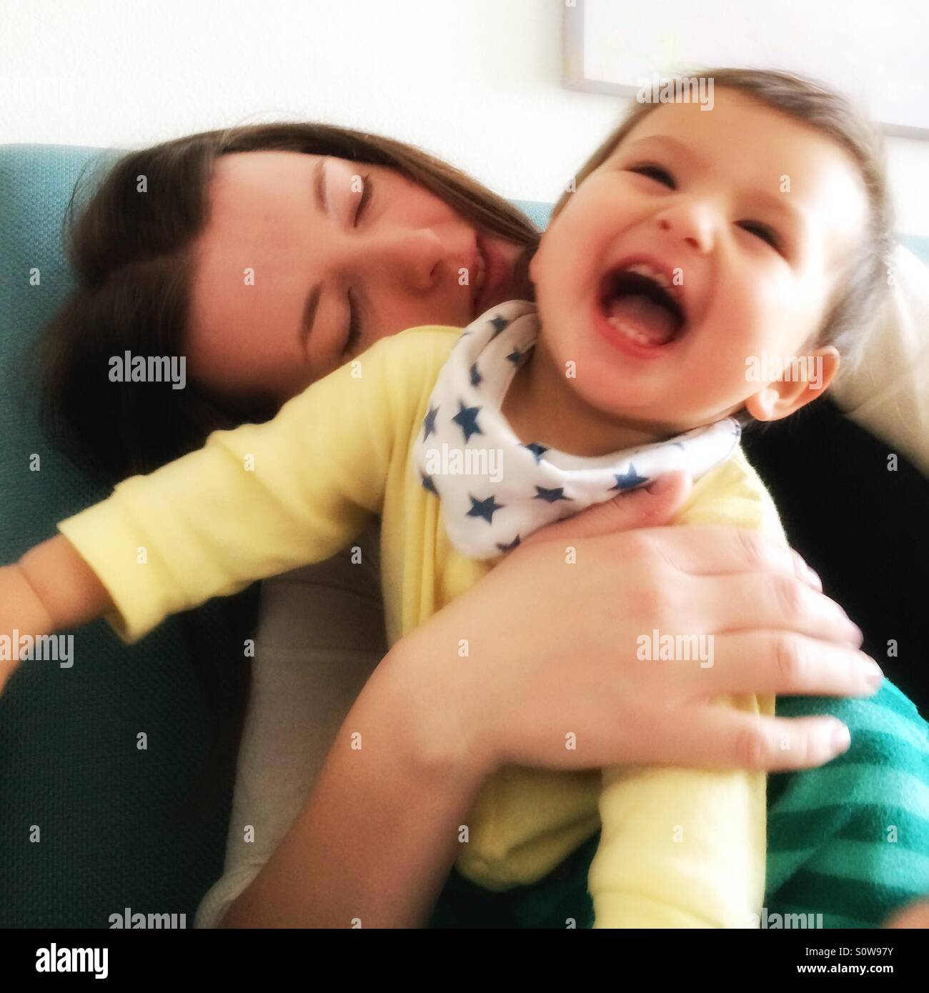 Mother playing with laughing baby - Stock Image