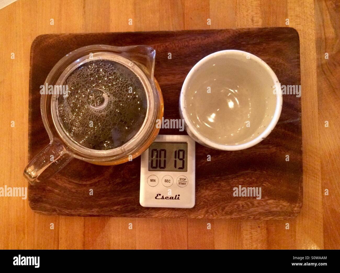 The timer is about to run out for some tea brewing at a local coffeehouse - Stock Image