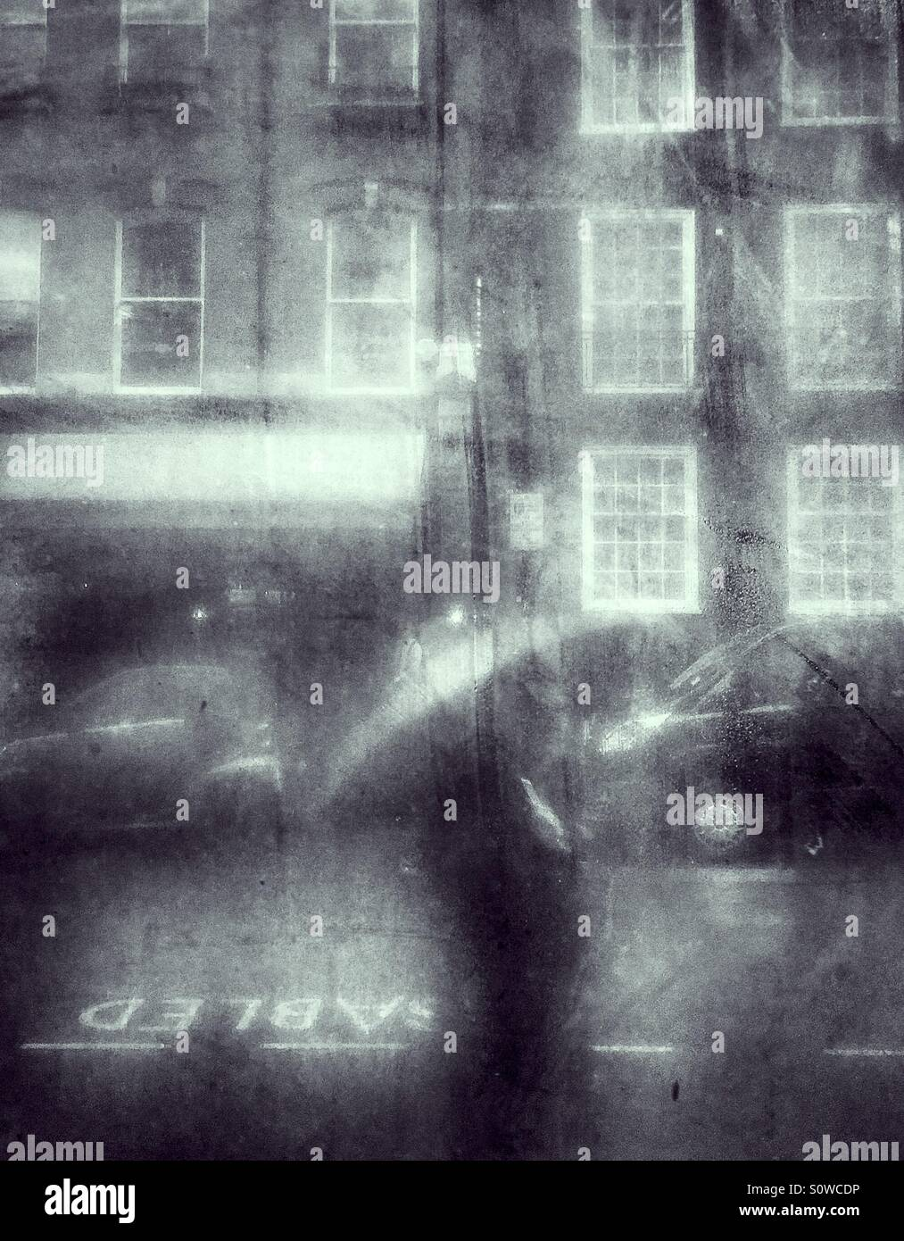 London Pedestrian with umbrella on a wet, miserable winters day, seen through a misty window. - Stock Image
