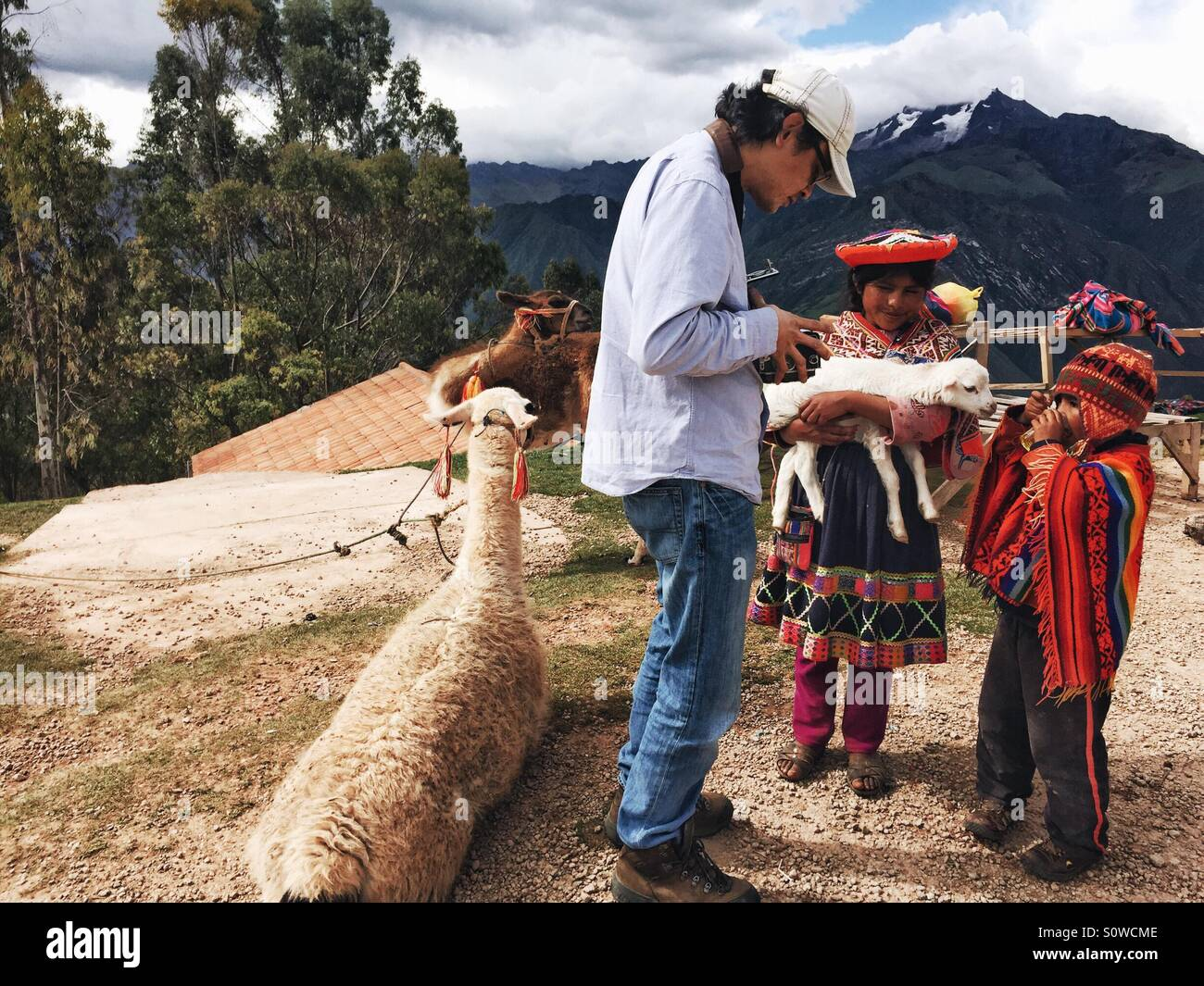 man photographing children in traditional clothes in Peru - Stock Image