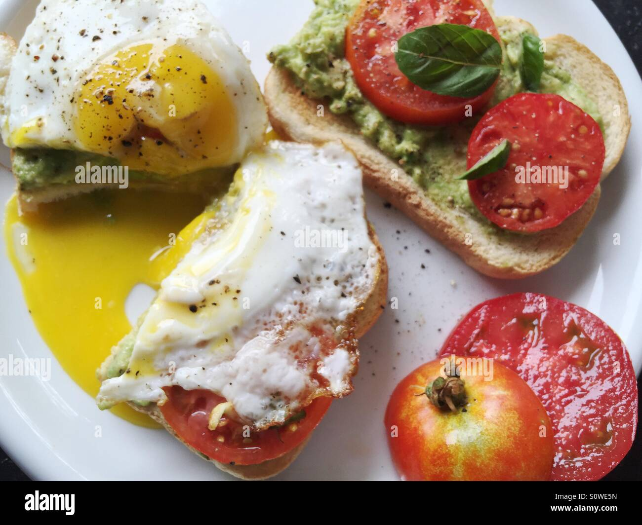 Fried egg with tomato and mashed avocado - Stock Image