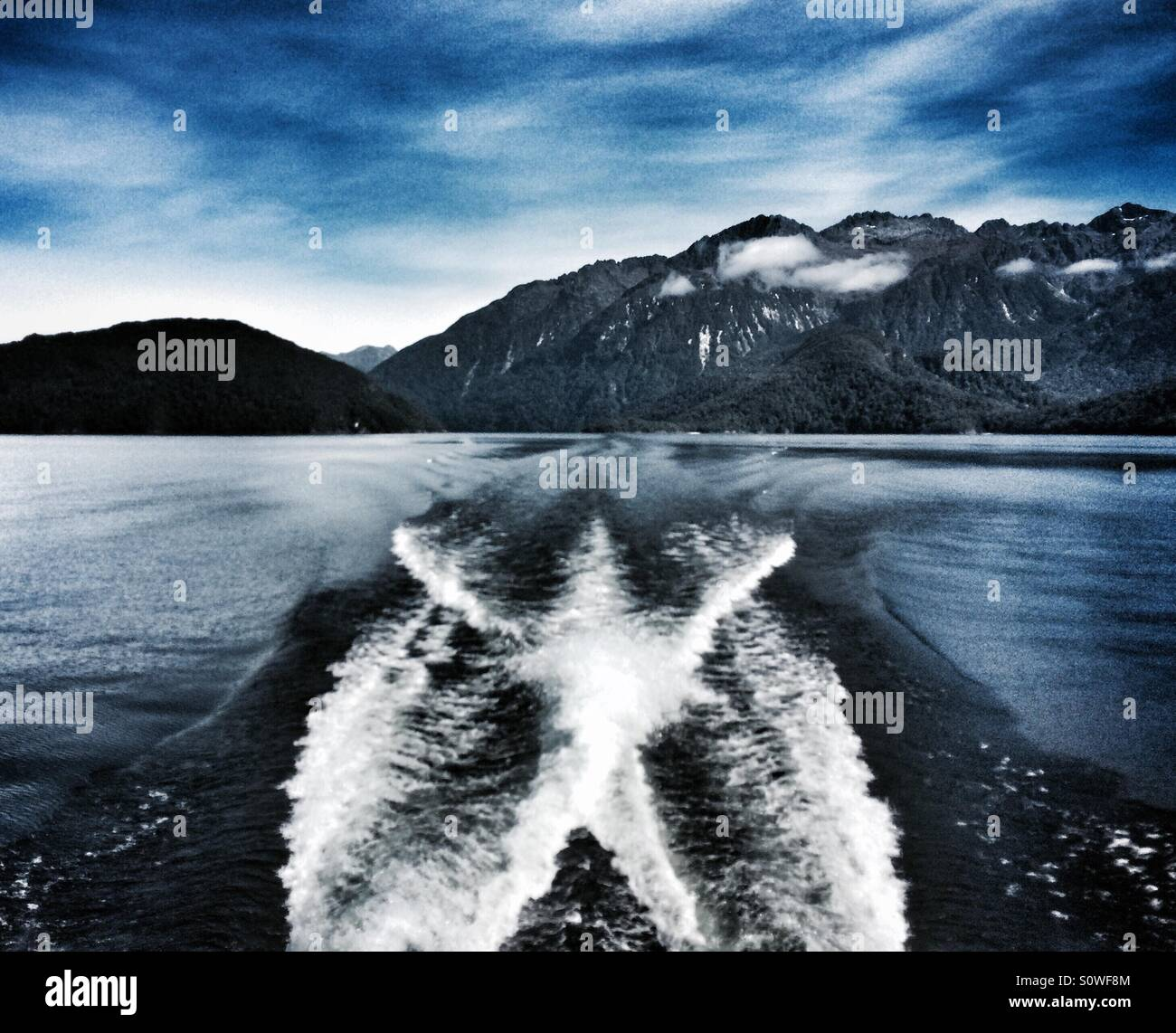 Trails behind a boat in Lake Manapouri, near Doubtful Sound, South Island, New Zealand Stock Photo