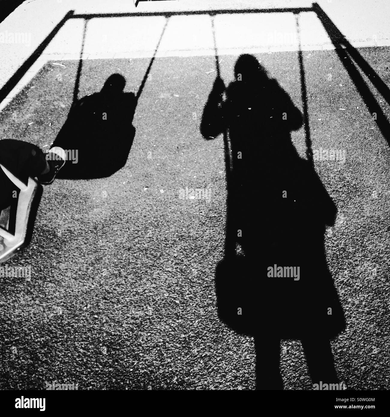 Shadow of Mum and toddler on swings - Stock Image