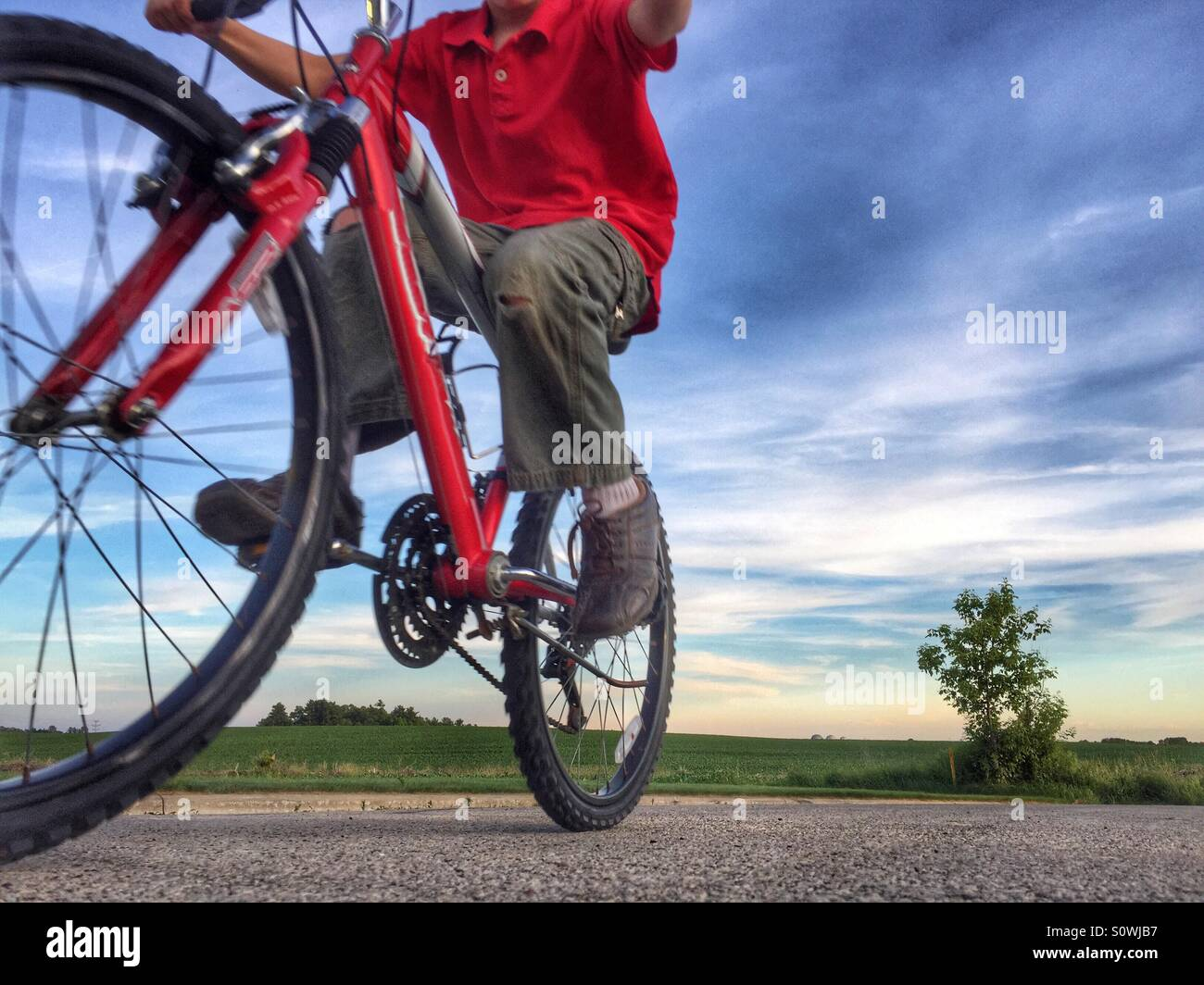 View looking up at a boy riding past on his red bicycle - Stock Image