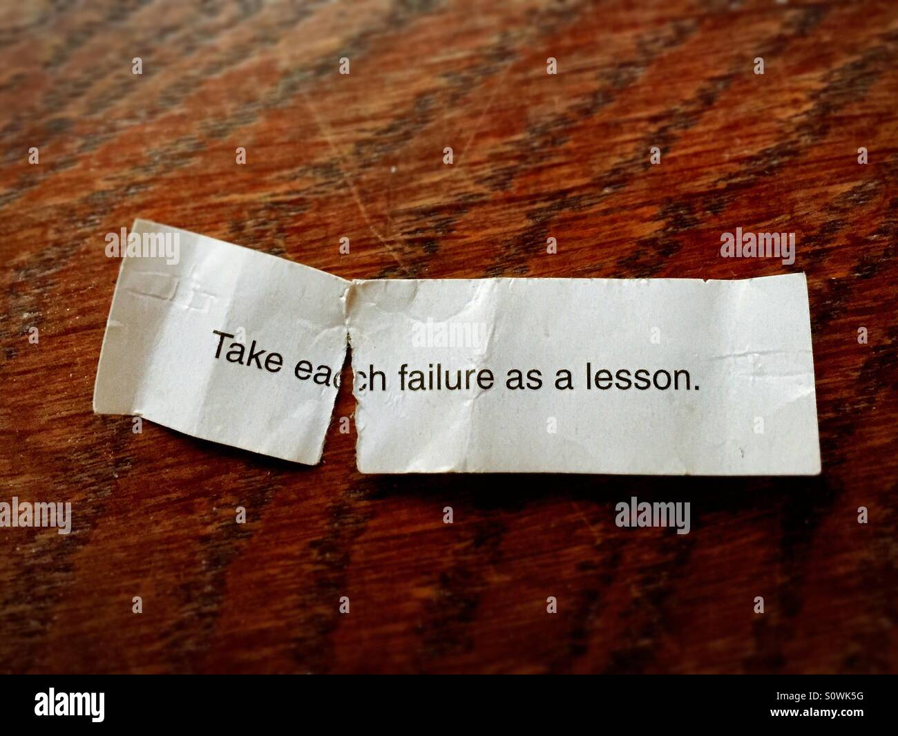 Take each failure as a lesson. Torn fortune cookie wisdom. - Stock Image