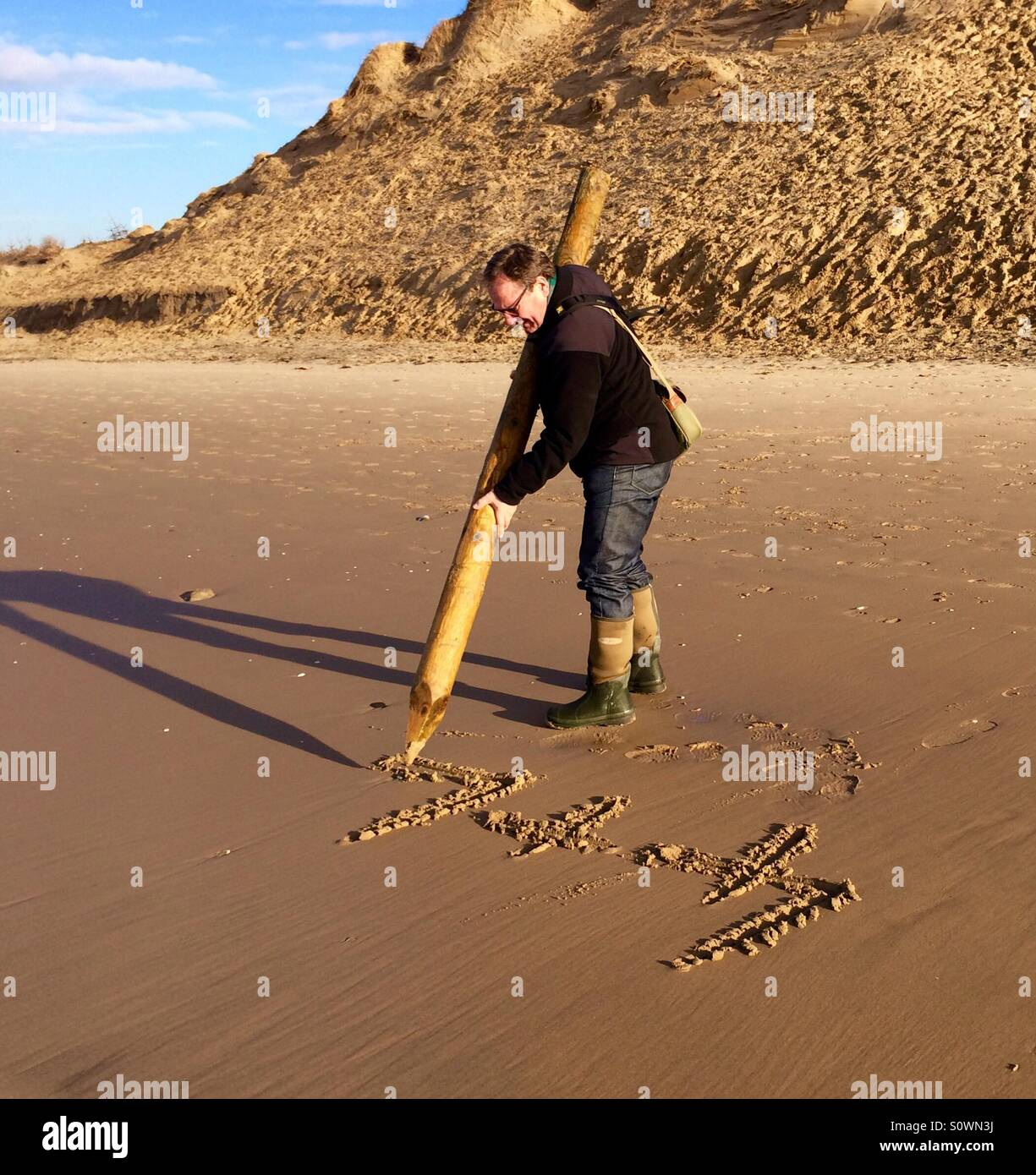 Writing with large pencil in the sand - Stock Image