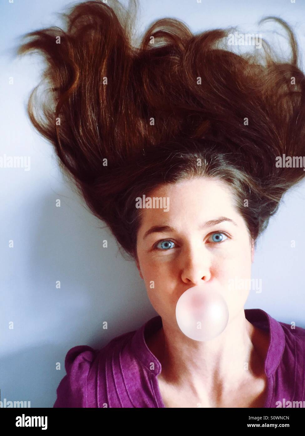 Woman with crazy hair blowing a bubble gum bubble Stock Photo