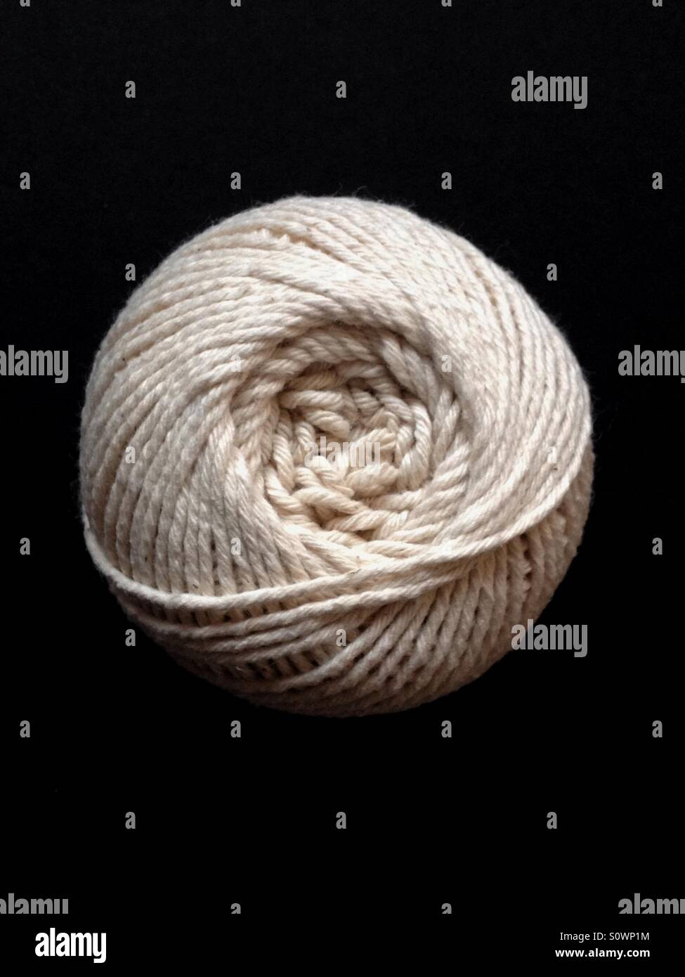 Ball of string on black background - Stock Image