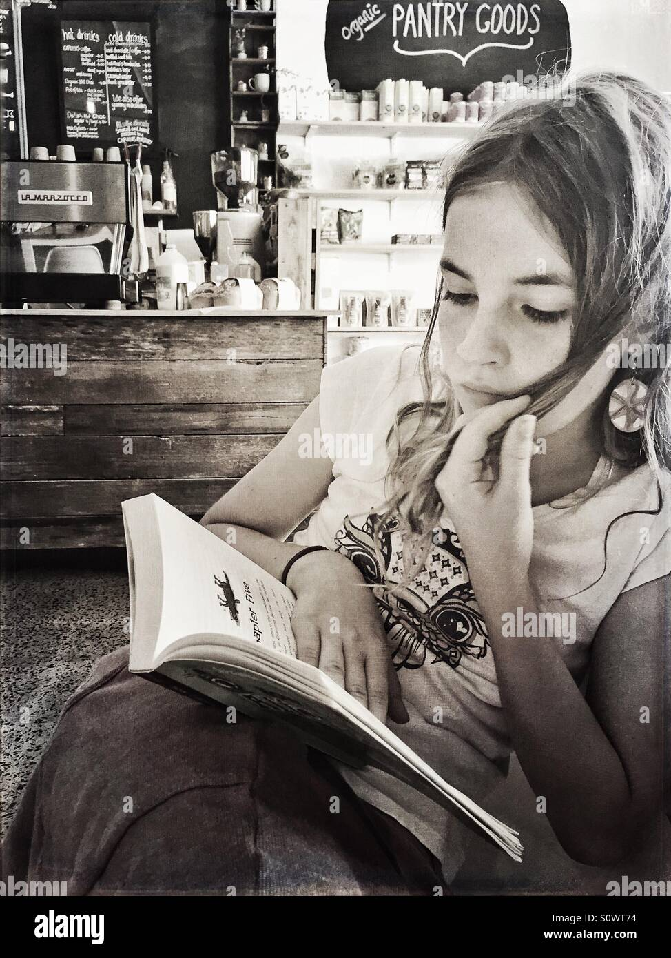 Black and white girl reading a book in rustic cafe - Stock Image