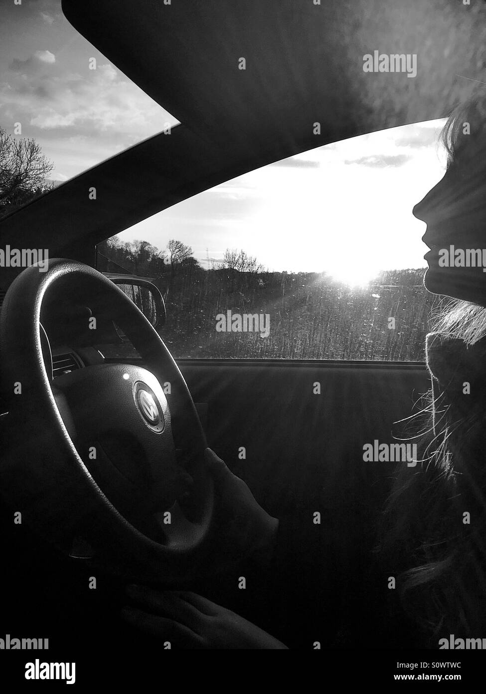 Woman driving Vw on sunny day - Stock Image