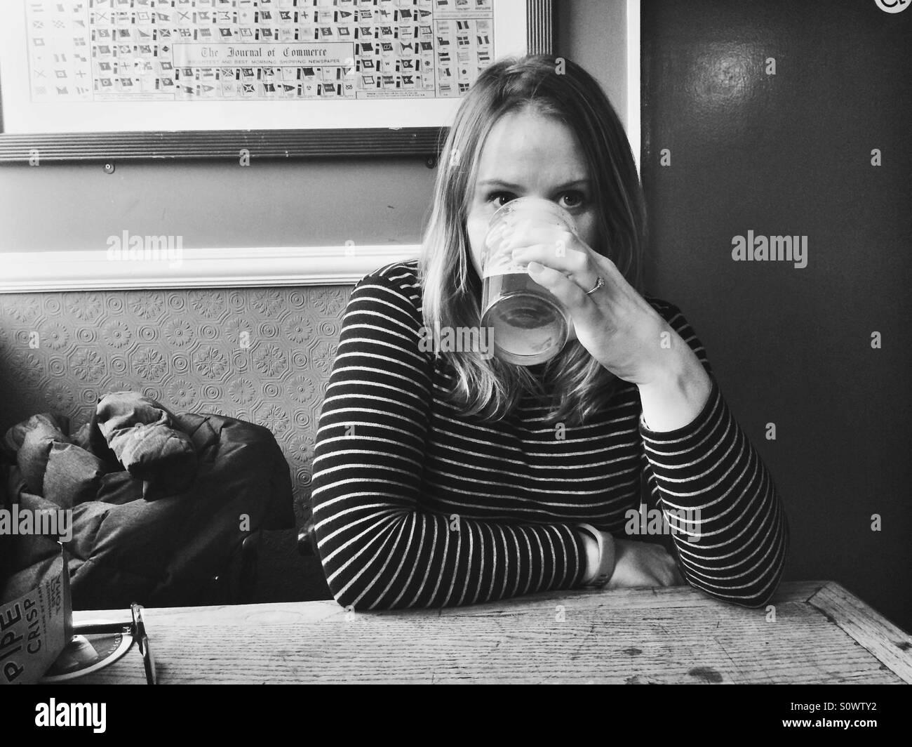Girl drinking a pint in a pub - Stock Image
