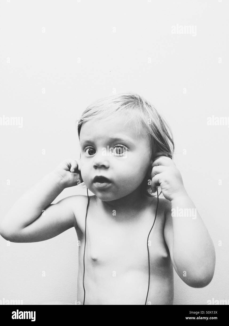 Baby girl listening to music. - Stock Image