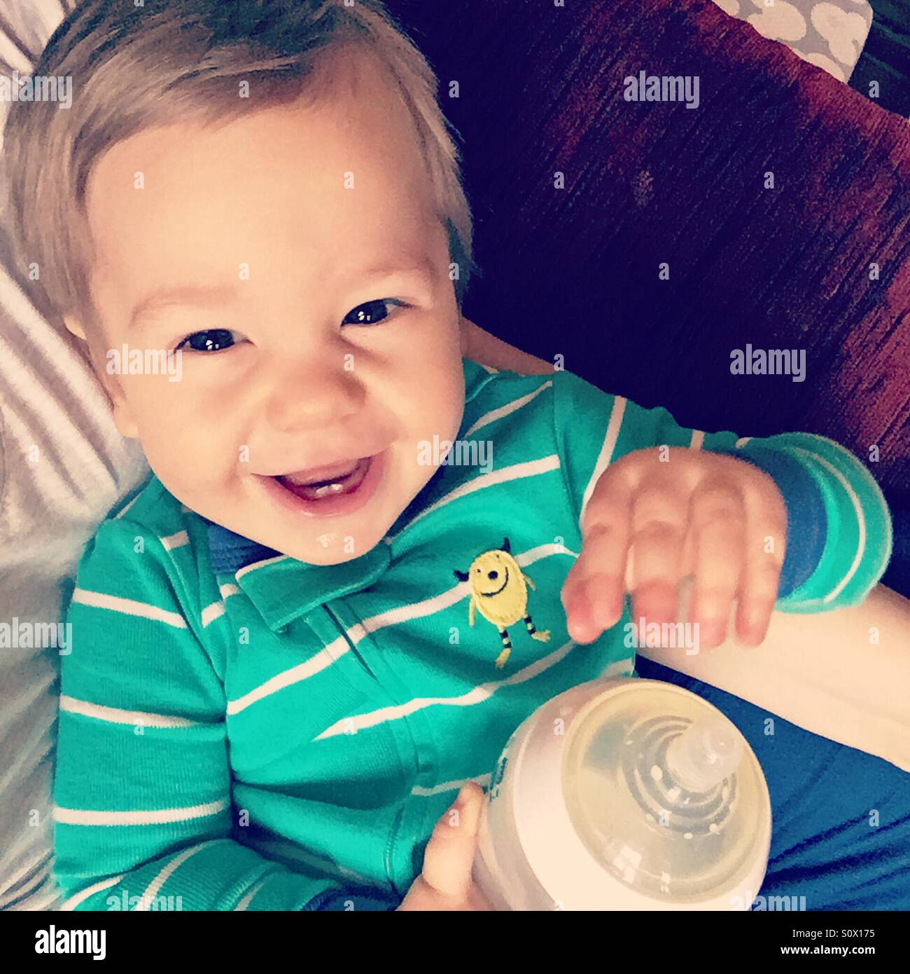 Baby boy wearing green stripe pajamas, holding a milk bottle, sitting on his mamas laps, smiling at the camera - Stock Image