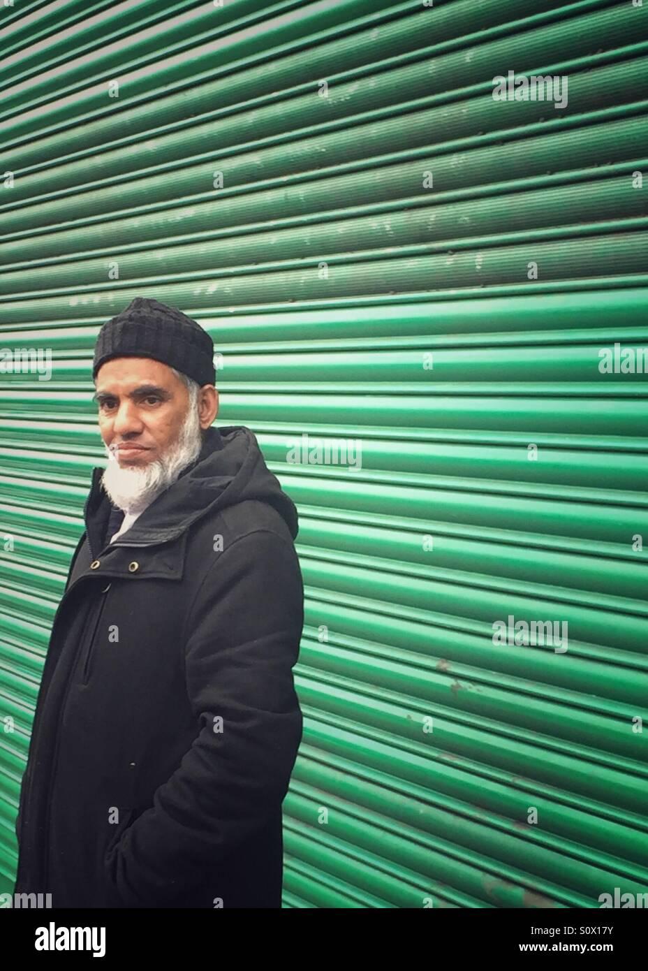 Portrait of a Bangladeshi man by green shutters in Whitechapel. London, U.K. - Stock Image