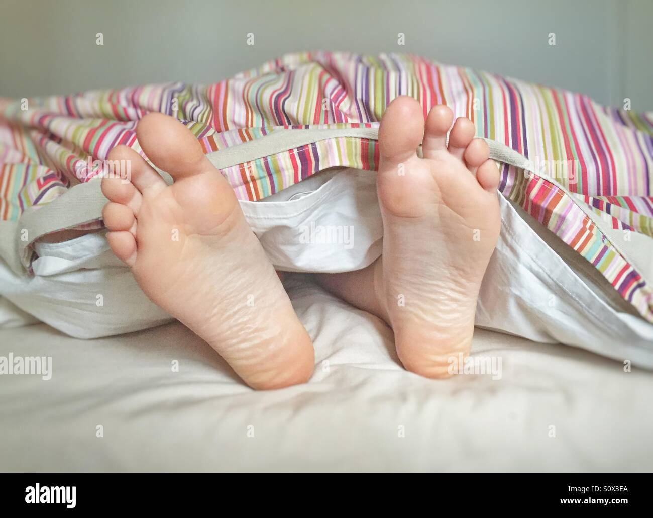 Wakey Wakey! Feet poking out from under the duvet cover - Stock Image